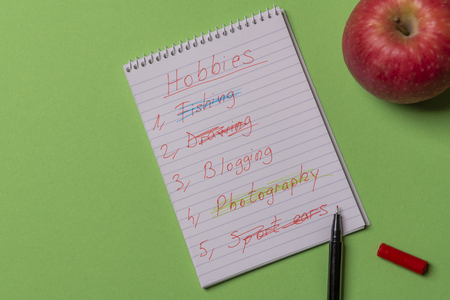 List of hobbies handwritten on a spiral notebook and a red apple on a green colored background. Directly above view with copy space