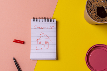 Shopping list with the only goal to buy a house. Childish house sketch draw on spiral notebook near a cup of coffee