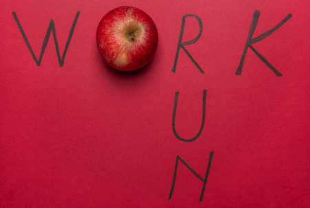 Work word wrote with an apple instead of the letter o and the word run, on a red background. Above view. Work, eat healthy and do sports concept. Imagens
