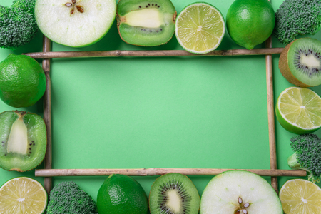 Above view of a frame made from fresh green fruits and broccoli, on a green table. Healthy eating frame. Detox context. Diet food. Vegetarian aliments.