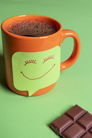 Fresh hot coffee in an orange mug and a funny smiley face sticky note on a green table beside a big piece of chocolate