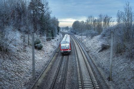 Duitse passagierstrein die bij zonsopgang door de besneeuwde natuur en bevroren bomen reist. Winter reiscontext. Modern openbaar vervoer. Stockfoto