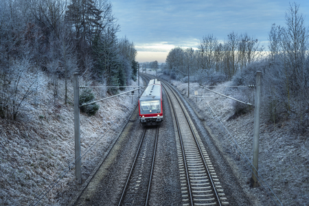 German passenger train traveling through snowy nature and frozen trees, at sunrise. Winter travel context. Modern public transportation.