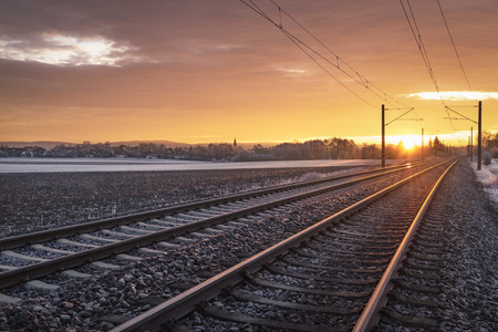 Railroad tracks through German countryside and snowy fields, at sunrise. Winter traveling concept. Train transport infrastructure. Stockfoto