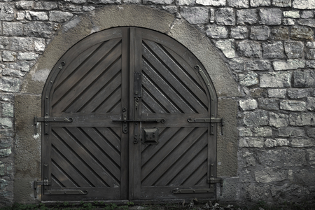 Closed wooden gate, a medieval structure with strong metal hinges and the stone wall from an ancient building Stockfoto
