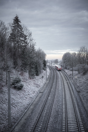 Rail tracks and German passenger train traveling through snowy nature, in a cold morning of December. Railway infrastructure. Public transport. Stockfoto