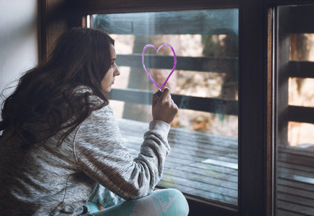 Millennial girl draws a heart with pink lipstick on a window.
