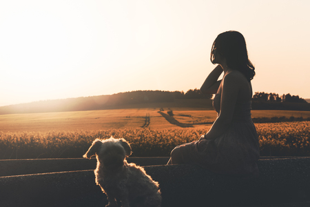 Millennial girl in a dress sitting with her dog, relaxing, near a rapeseed field, at sunset, in South Moravia region, Czech Republic.