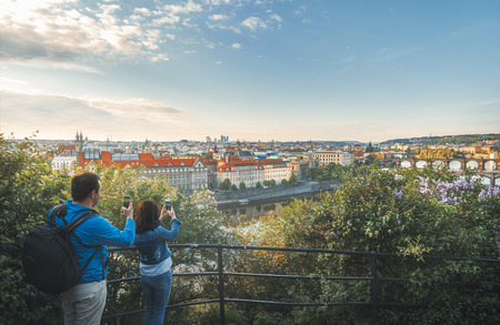 Young woman and man in casual clothes with smartphones in hands taking photos of the Prague city, at sunrise, in the Czech Republic.