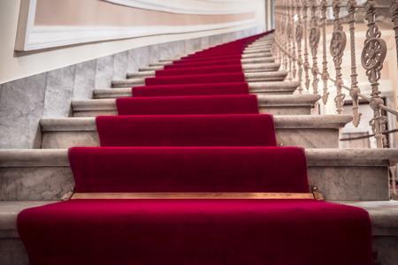 Luxuriöses Gebäudeinnere mit Marmortreppe, die mit einem roten Teppich bedeckt ist Standard-Bild