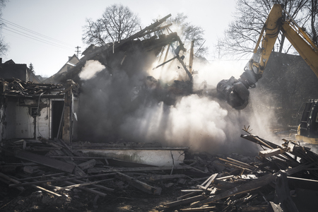 Demolition of an old German house with an excavator. House crashing in a dust cloud and sun rays. Construction site. Stock Photo