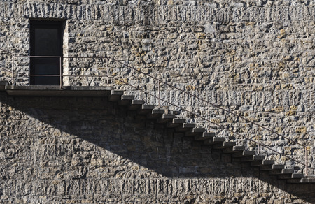 Minimal image of an exterior staircase and door on a stone wall building. Vintage architecture in a minimalist concept.