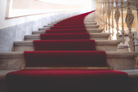 Royal building interior with the red carpet on the marble stairways in a luxurious and elegant building