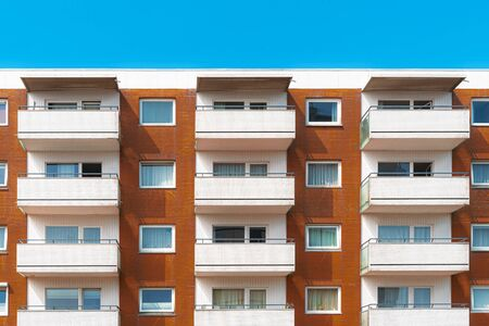 Orange and white facade of an apartment building with balcony and windows and blue sky. German architecture on sunny day.