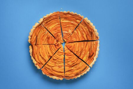 Above view of a sweet potato pie, sliced in eight, on a blue background. Flat lay of slices of orange autumn pie. Traditional American food.