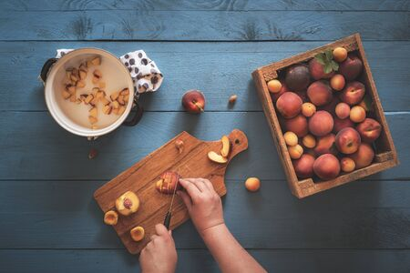 Woman hands cutting into pieces peaches and apricots from a vintage wooden box, on a blue kitchen table. Above view with the making of peaches jam.