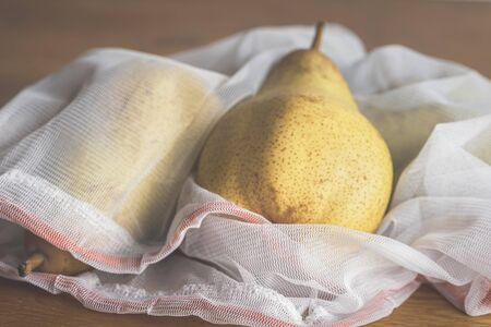 Ecological lifestyle concept with fresh fruits in reusable shopping bags. Eco-friendly mesh bag with pears in it. Reduce plastic packaging concept.