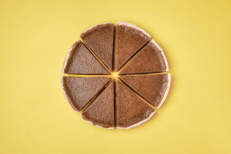 Homemade american pie. Flat lay of a pumpkin pie, cut in slices, on a yellow background. Minimal image of Thanksgiving dessert. Sliced pumpkin cake.