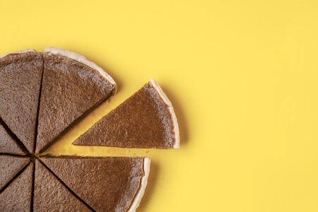 Tasty autumn pumpkin pie, sliced in pieces on a yellow background and one slice separated. Thanksgiving traditional dessert. Minimal sweet food image