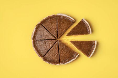 Kuchenscheiben getrennt vom ganzen Kürbiskuchen auf gelbem Grund. Flache Lage des traditionellen amerikanischen Kuchens. Minimales Thanksgiving-Essen. Süßes Gebäck