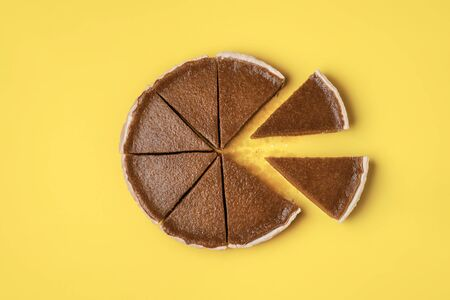 Pie slices separated from the whole pumpkin pie on a yellow background.  Flat lay of traditional American pie. Minimal Thanksgiving food. Sweet pastry