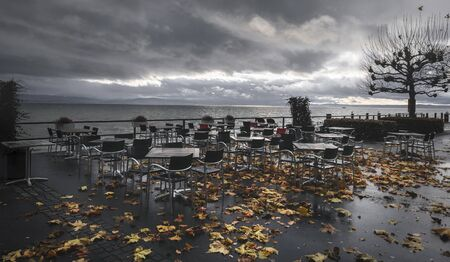 Autumn outdoor scenery with empty tables and wet chairs, on the terrace of a restaurant on the shore of Lake Constance, in Friedrichshafen, Germany.