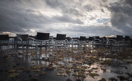 Gloomy autumn with orange fallen leaves among empty tables and wet chairs on a veranda, on a rainy day of November, on Constance lakeshore, Germany.