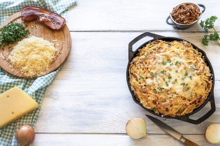 Home cooking of Bavarian spaetzle with cheese and bacon. Above view of ingredients for German traditional Oktoberfest food Cheese pasta on white table