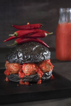 Spicy hamburger with black bread buns and Swedish meatballs and tomato sauce on a black plate and dark decor. Strange burger. Halloween food. 写真素材