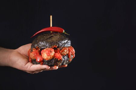 Black bread bun burger with Swedish meatballs and spicy tomato sauce, held in hand on black background. Strange hamburger and hot pepper in hand.