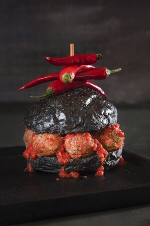 Black bread hamburger with meatballs and spicy tomato sauce on a black plate and table. Low light strange burger image. Weird food. Halloween dish. 写真素材