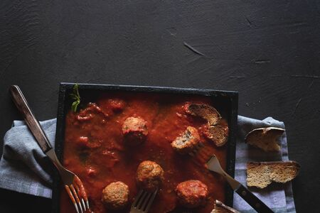 Meatballs dish in tomato sauce on a kitchen towel and black table. Above view of meatballs family dinner. Flat lay of the eaten dinner meal.