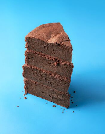 Brownie cake slice tower on a blue background. Kladdkaka Fika cake slices stack. Minimal image of Swedish sticky chocolate cake pile from 4 pieces.