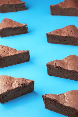 Swedish sticky chocolate cake slices, in a pattern on a blue background. Kladdkaka pieces, symmetrically displayed. Brownie cake portions.