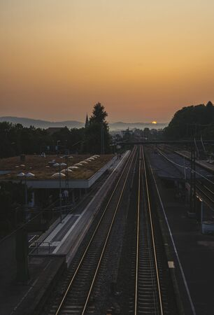 Train station and railroads at sunrise. Railway lines leading towards the horizon. Strong morning sun on the clean sky 版權商用圖片