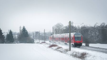 Winter scenery with a red train traveling near a village. Passengers train on the snowy railroad.