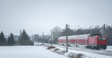 Winter scenery with a passenger train on the snowy railroad.  Red train traveling in a winter decor 版權商用圖片