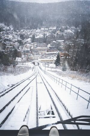 Traveling funicular railway vehicle and window view of the snowy railroad tracks, the snowy forest, and a snow-covered Bad Wildbad town, in Germany.