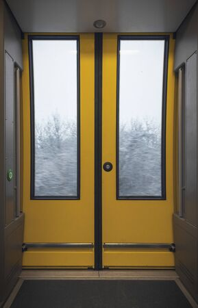 Automatic yellow doors from a modern train. Interior of a german passengers train with the corridor and sliding door