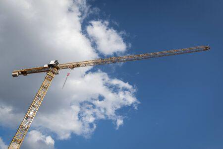 Tower crane under the blue sky. Yellow crane on construction site under a fluffy white cloud Reklamní fotografie
