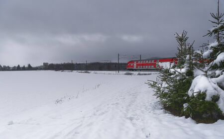 Red train traveling through the snowy fields. Winter scenery with the snow-covered trees and fields and a german passengers train 版權商用圖片