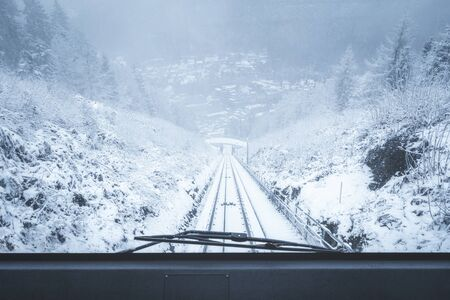 Moving funicular vehicle windshield view with snow-covered nature scenery in Bad Wildbad, Black Forest, Germany, on a snowy day of January.