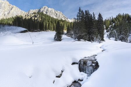Winter landscape in the Austrian Alps. Frozen creek surrounded by snowdrifts and snowy pine trees.