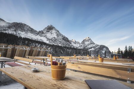 Winter scenery with an outdoor restaurant with wood tables and snow-covered peaks of the Austrian Alps mountains, in December, in Ehrwald, Austria.