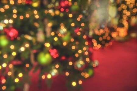Christmas tree blur background with bokeh lights. Xmas lights on a pine tree on a red background. Christmas concept. Christmas lights background.