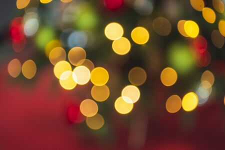 Colorful Christmas background with blur Christmas tree lights on a red backdrop. Xmas pattern. Christmas tree lights. Winter holiday blurred backdrop