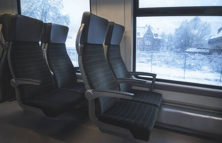 Eco-friendly public transport image with comfortable train seats and window view with snowy scenery. Winter traveling. German modern train interior.
