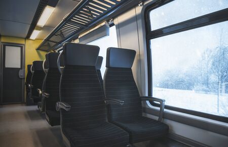 Winter traveling concept with a german train interior with black seats, in a row, and a window view with a snowy nature landscape, on a snowstorm.