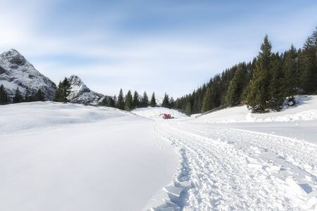 Winter snowy landscape with snow-capped Alps mountains peaks, fir forest, and snow-covered fresh road. Snowmobile tracks snow road. Ehrwald, Austria.