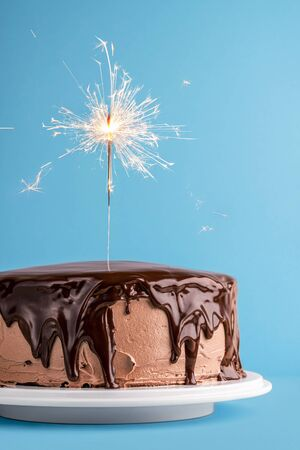 Lit sparkler on birthday cake with cocoa buttercream and melted chocolate glaze, on blue background. New year concept with festive cake and firework.